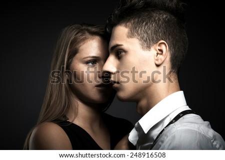 Portrait of fashion couple against grey background - stock photo