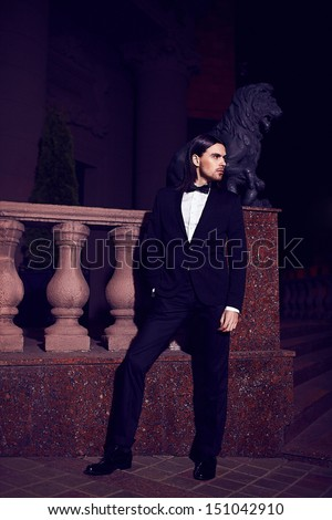 Portrait of fashion elegant long-haired young caucasian sexy muscled attractive handsome man model businessman in black costume with moustache in the street at night - stock photo