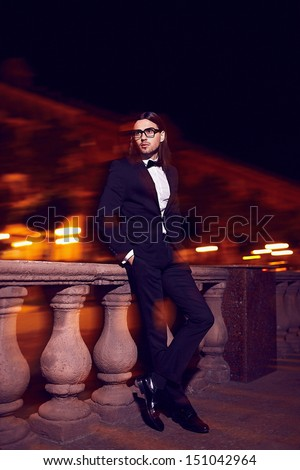 Portrait of fashion elegant long-haired young caucasian sexy muscled attractive handsome man model businessman in black costume with moustache in the street at night in glasses - stock photo