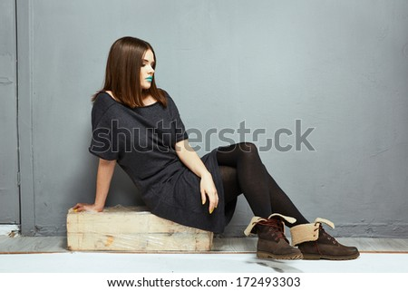 Portrait of fashion full body model seating against gray wall. Teenager style.