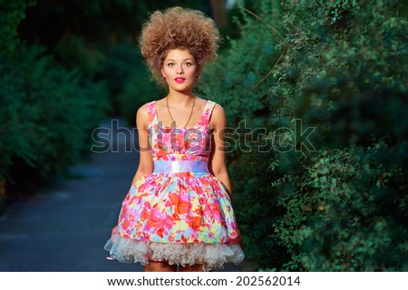 Portrait of fashion girl in pink dress and hairstyle in park. - stock photo