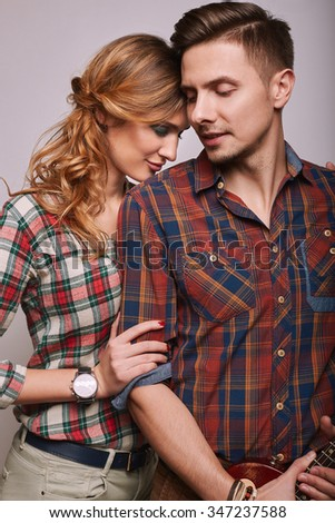 Portrait of fashion glamor stylish hipster young couple wearing shirts in studio - stock photo