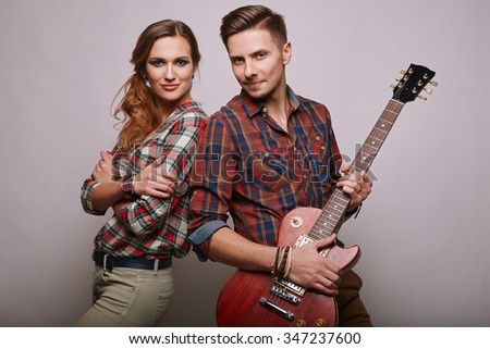Portrait of fashion glamor stylish hipster young couple wearing shirts with guitar in studio - stock photo