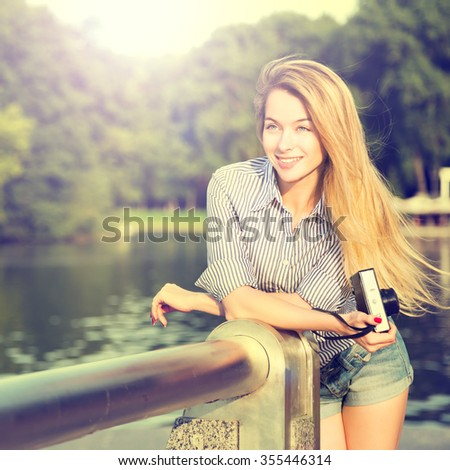 Portrait of Fashion Hipster Girl with Vintage Camera Standing by the River. Modern Teenage Lifestyle Concept. Instagram Styled Toned and Filtered Photo. - stock photo