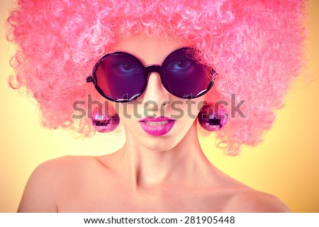 Portrait of Fashion hipster nude girl in sunglasses with trendy afro hairstyle on yellow background. Punk girl with earrings like disco ball. Sexy provocative party look. Seductive woman, sensual lips - stock photo