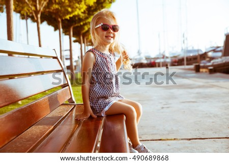 Portrait of fashion little girl in a park, leisure the nature. Blonde princess  Happiness, fashionable concept.