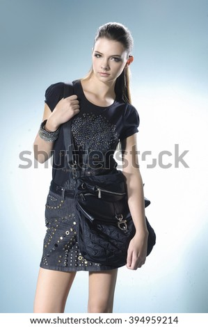 Portrait of fashion model with bag posing in light background - stock photo