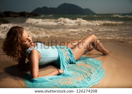 Portrait Of Fashion Woman In Blue Dress Lying On Sand Tropical Beach - stock photo
