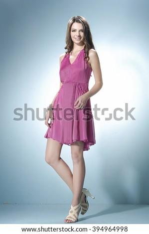 Portrait of fashion young woman walking in studio - stock photo