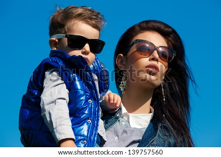 Portrait of fashionable baby boy and his gorgeous mother (hollywood star) in trendy sunglasses walking in the street. Sunny spring day. Outdoor shot - stock photo