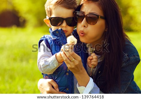 Portrait of fashionable baby boy and his gorgeous mother in trendy sunglasses playing with dandelion in the park. Sunny spring day. Close-up. Copy-space. Outdoor shot - stock photo