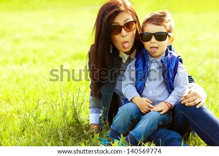 Portrait of fashionable baby boy and his stylish mother in trendy sunglasses playing and showing tongues in the park. Sunny spring day. Hipster style. Copy-space. Outdoor shot