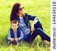 Portrait of fashionable baby boy and his stylish mother in trendy sunglasses sitting on green grass in the park. Sunny spring day. Hipster style. Outdoor shot - stock photo