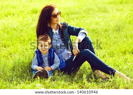 Portrait of fashionable baby boy and his stylish mother in trendy sunglasses sitting on green grass in the park. Sunny spring day. Hipster style. Copy-space. Outdoor shot