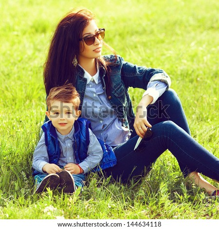 Portrait of fashionable baby boy and his stylish mother in trendy sunglasses sitting on green grass in the park. Sunny spring day. Hipster style. Outdoor shot