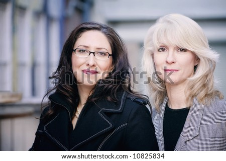 Portrait of fashionable brunette and blonde businesswomen - stock photo