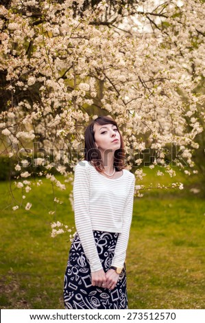 Portrait of fashionable brunette girl with beautiful brown eyes.Cherry blossoms on a background - stock photo