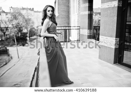 Portrait of fashionable girl at red evening dress posed background mirror window of modern building on the terrace balcony. Black and white photo