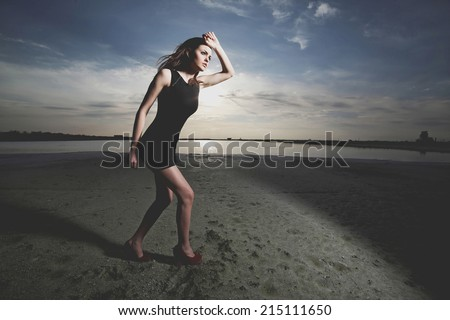 Portrait of fashionable girl running at the seaside .Fashio colors. Wide angle.