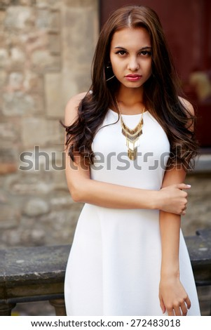Portrait of fashionable gorgeous female model in white dress looking to the camera, attractive woman with beautiful curly brunette hair posing outdoors, sexy charming woman looking to you - stock photo