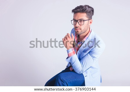 portrait of fashionable man, seated, wearing glasses while thinking and looking away in studio background - stock photo