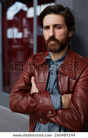 Portrait of fashionable mature hipster man dressed in pattern shirt and leather jacket standing with crossed arms indoors while look to the camera - stock photo