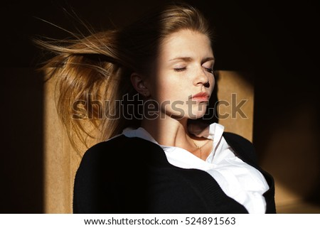 Portrait of fashionable model with long hair in black jacket, white shirt having a rest in office. Natural style. Daylight. Close up. Studio shot