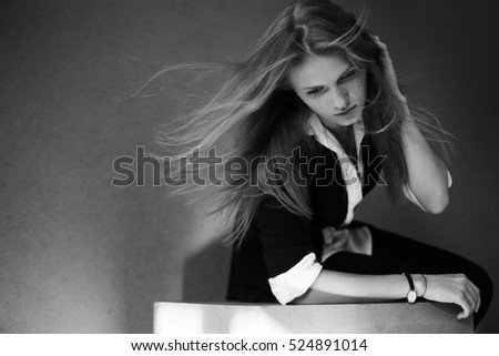 Portrait of fashionable model with long hair in black jacket, white shirt, posing over wooden background. Natural style. Daylight. Copy-space. Monochrome studio shot