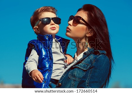 Portrait of fashionable mother hugging her gorgeous baby boy in trendy sunglasses. Family walking in the street. Stylish casual clothes. Sunny spring day, blue sky. Outdoor shot