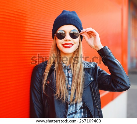 Portrait of fashionable smiling woman wearing a rock black style having fun outdoors in the city - stock photo