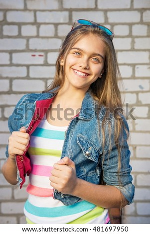 Portrait of fashionable teen girl with long hair on background of brick wall. Portrait of  happy teen girl. beautiful girl