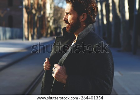 Portrait of fashionable well dressed man with beard posing outdoors looking away, confident and focused mature man in coat standing outside at sunny evening, elegant fashion model - stock photo