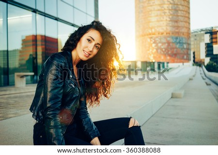 Portrait of fashionable well dressed woman with long curly hair posing outdoors and looking at camera. flare light - stock photo