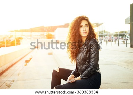 Portrait of fashionable well dressed woman with long curly hair posing outdoors and looking away. flare light - stock photo