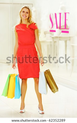 Portrait of fashionable woman holding paperbags and standing near showcase with title ?sale - stock photo
