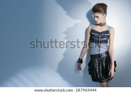 Portrait of fashionable woman posing in light background - stock photo