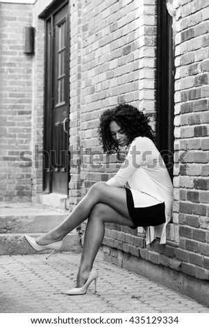 Portrait of fashionable young attractive black woman with afro in urban background
