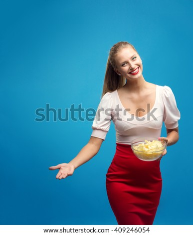 Portrait of fashionable young blond woman in pink-red dress, bright make-up holding, eating fried potato, chips and  over blue background. Copy-space. Unhealthy eating. Junk food concept.  - stock photo