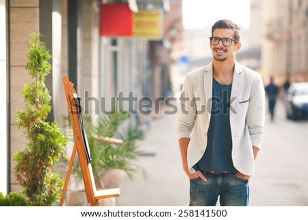 Portrait of fashionable young man standing on the street with hands in his pockets.