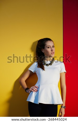Portrait of fashionable young woman posing on colored wall background with copy space for your text message while looking to the camera, stylish teenager girl posing on bright background - stock photo