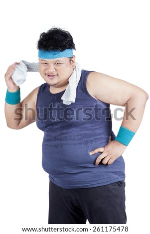 Portrait of fat person wearing sportswear and wiping his sweat with a towel, isolated on white - stock photo