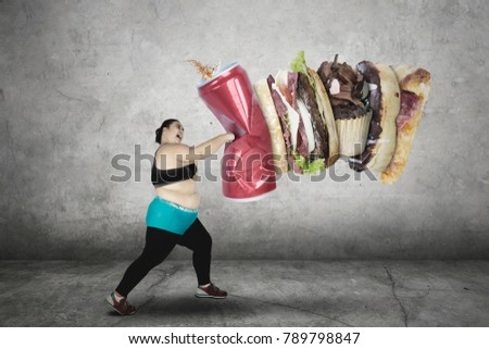 Portrait of fat woman hitting fast food while wearing sportswear. Shot in the studio