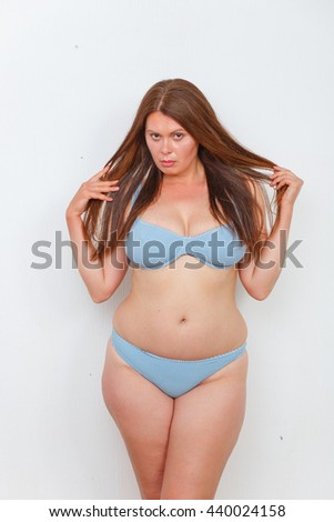 Portrait of fat woman in underwear or lingerie posing in studio. Red haired lady on diet looking sad and disappointed. - stock photo