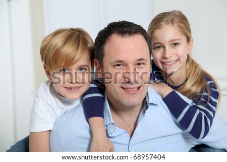 Portrait of father and children at home - stock photo