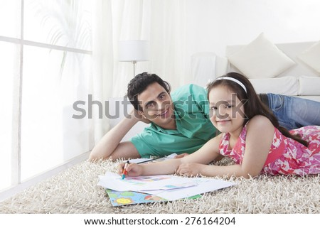 Portrait of father and daughter drawing while lying on rug at home - stock photo