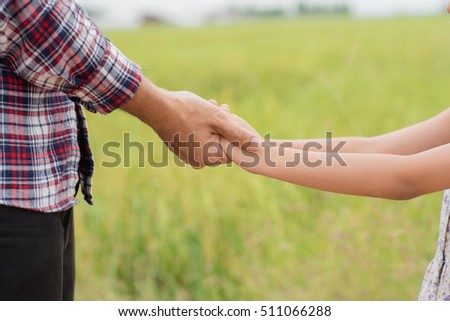 Portrait of Father and daughter holding hand in hand on field.