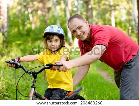 portrait of father and daughter on a bicycle in the park