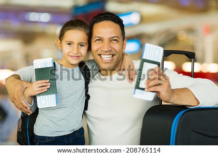 portrait of father and pretty daughter at airport travelling together - stock photo