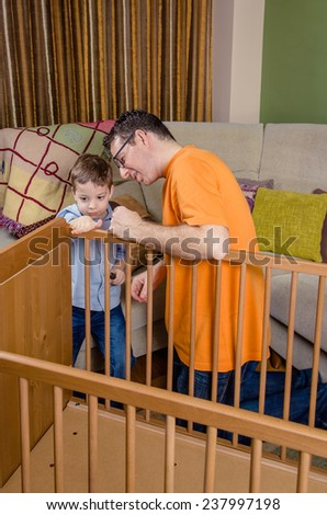 Portrait Of Father And Son Assembling Together Cot For A Newborn At Home.  Family Leisure