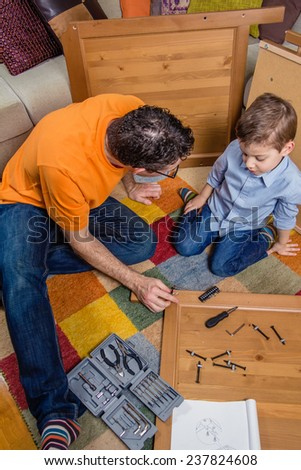 Lovely Portrait Of Father And Son Assembling With Tools A New Furniture For Home.  Family Leisure